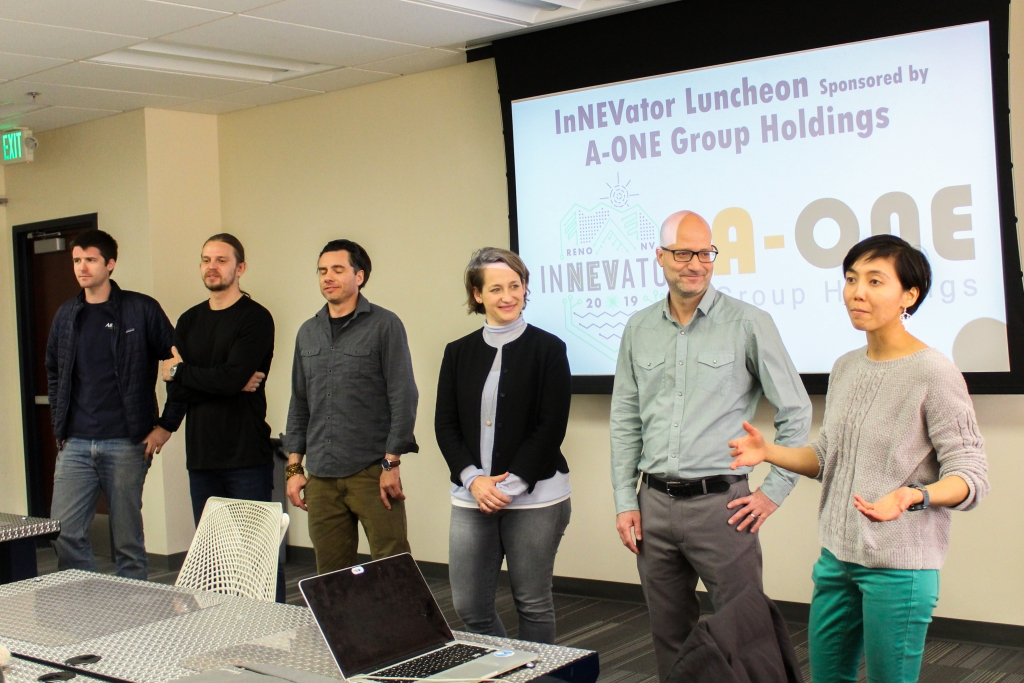 Six people stand at the front of the room, they are the InNEVator cohort of the Spring 2019 Program. There is a powerpoint slide in the background.