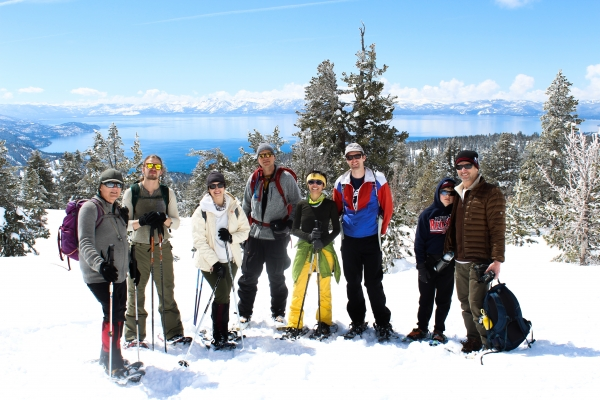 A group photo of the Spring 2019 InNEVator group snowshoeing with Lake Tahoe in the background.