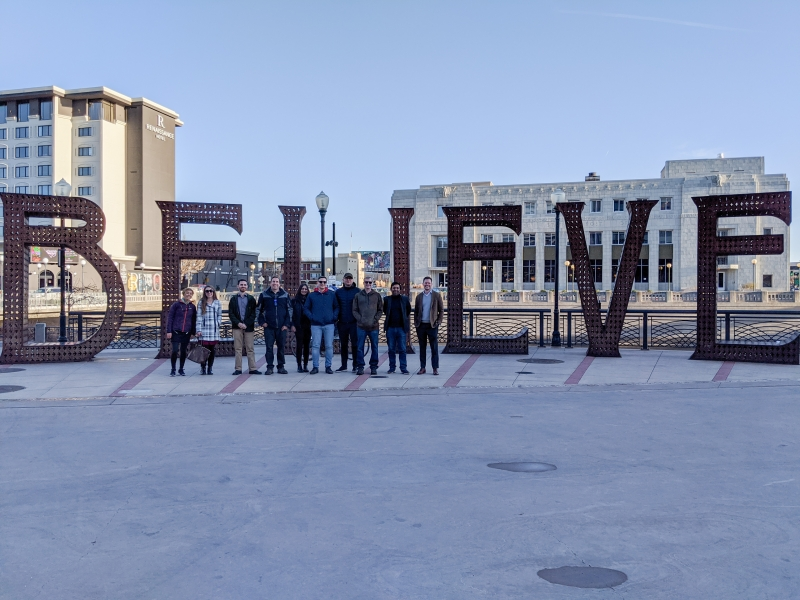 Group of people standing in front of a believe sign