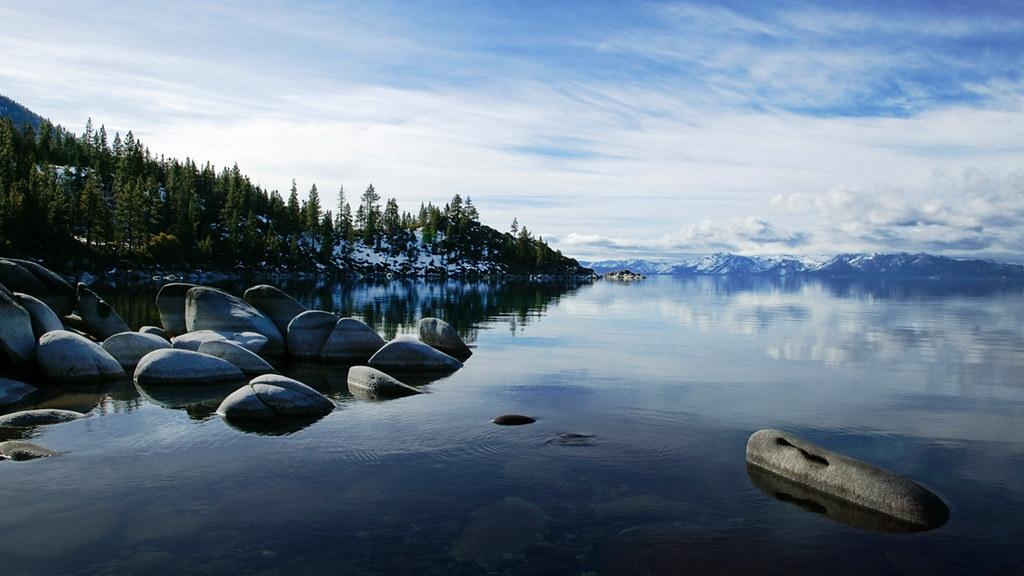 Lake Tahoe photo. A serene lake alpine like with large boulders protruding, trees on a peninsula in the background, snowcapped mountains in the distance, and a blue sky with wispy white clouds.