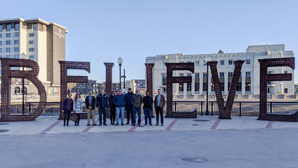"""A group photo of 10 people standing outside in front of a large sculpture that spells the word """"Believe"""". There are buildings in the background, a blue sky, and it looks chilly outside."""